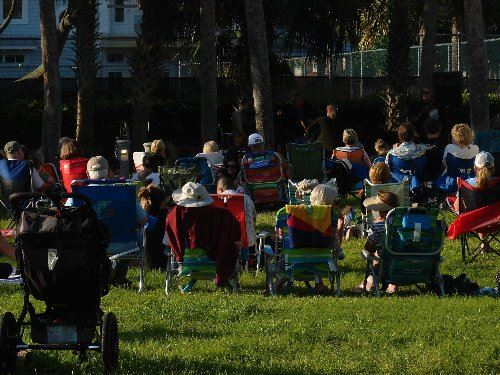 Patrons in lawn chairs enjoying music in the park.